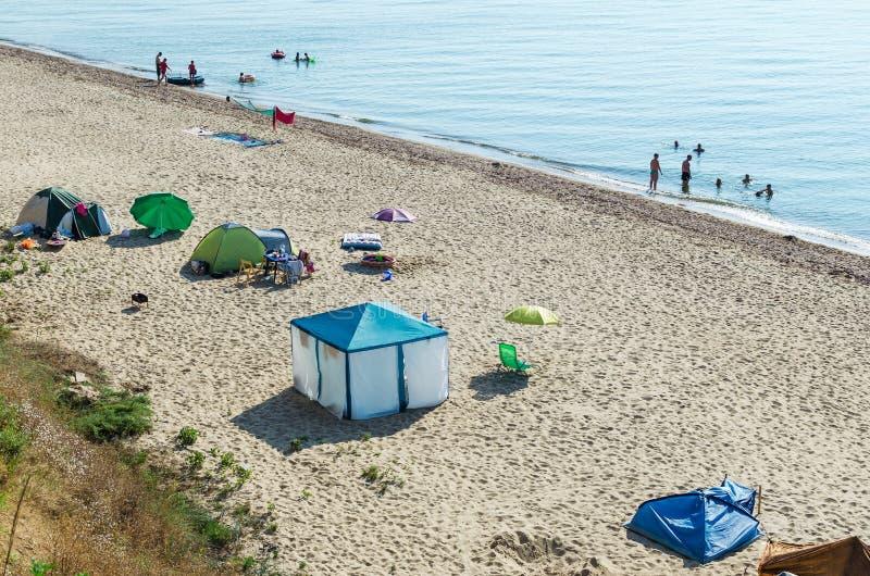 As barracas e o equipamento para acampar estão na praia do mar fotografia de stock royalty free