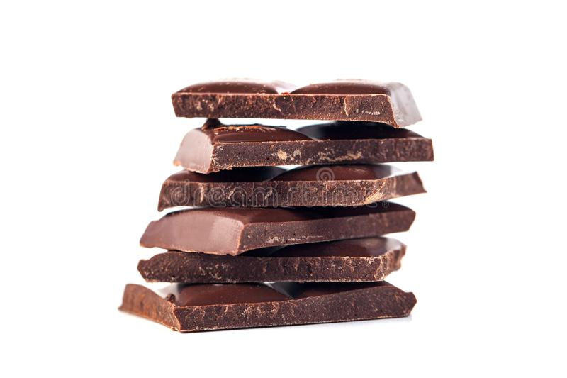 As barras de chocolate escuras empilham isolado no fundo branco fotos de stock royalty free