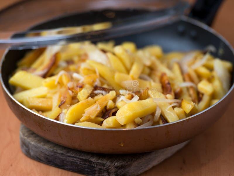 As batatas fritadas caseiros apetitosas com cebolas serviram em uma frigideira fotografia de stock royalty free