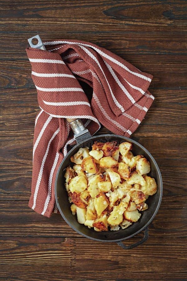 As batatas fritadas, batatas do café da manhã, ferro fundido, batata triturada, foto conservada em estoque, em uma frigideira, ce imagem de stock