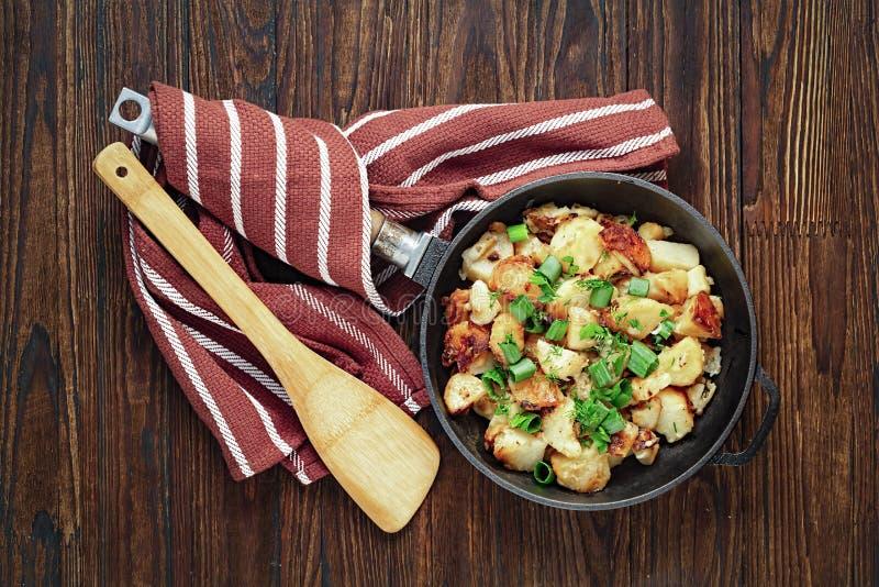 As batatas fritadas, batatas do café da manhã, ferro fundido, batata triturada, foto conservada em estoque, em uma frigideira, ce fotos de stock