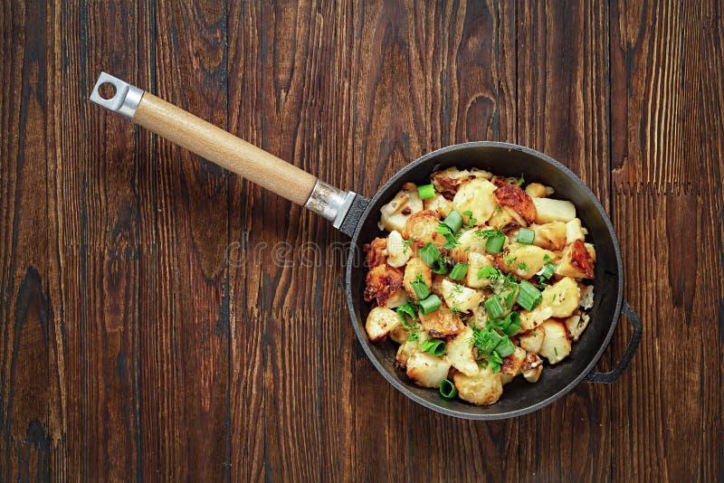 As batatas fritadas, batatas do café da manhã, ferro fundido, batata triturada, foto conservada em estoque, em uma frigideira, ce imagens de stock