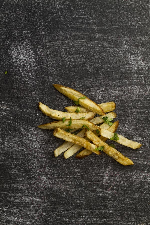 As batatas fritas arejam o prato exterior fritado na tabela gasta preta fotografia de stock royalty free