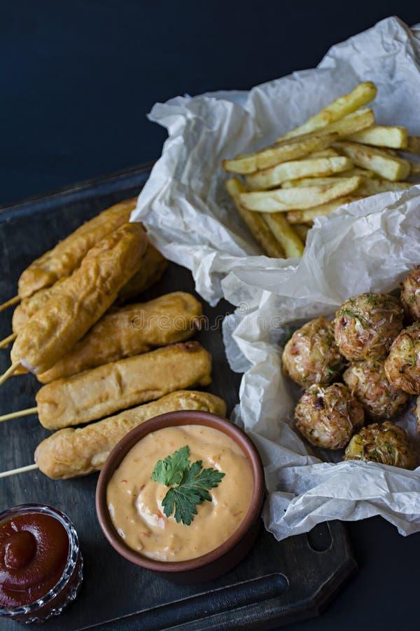As batatas fritas fritadas, do ¡ de Ð cão e croquetes e batatas alaranjados da couve com molho e ketchup são decorados com legume foto de stock
