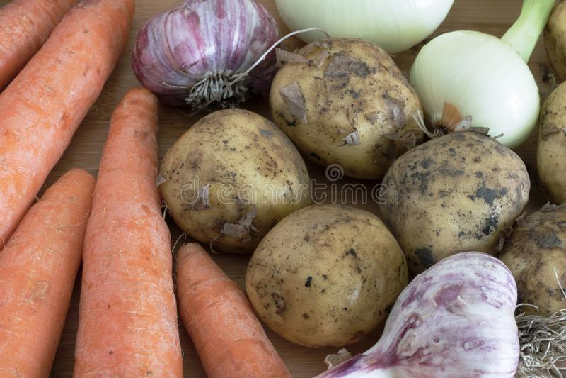 As batatas que encontram-se em uma tabela de madeira ao lado das cenouras, do alho e das cebolas complementam a composição dos ve fotografia de stock royalty free