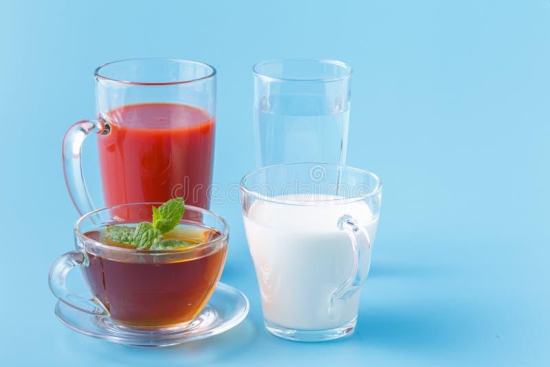 As bebidas coloridas úteis do grupo bebem o chá Juice Water do leite no fundo azul foto de stock royalty free