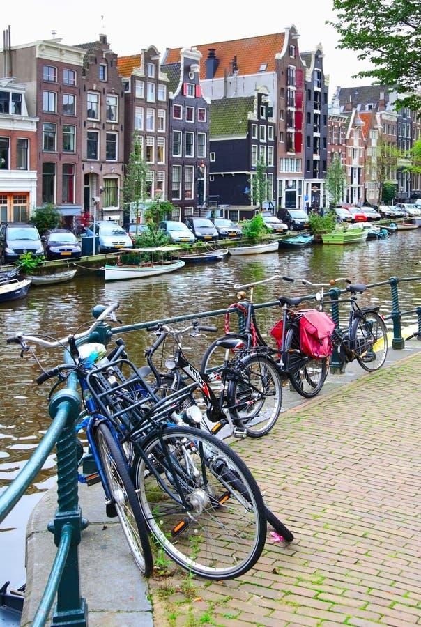 As bicicletas aproximam o canal em Amsterdão fotografia de stock