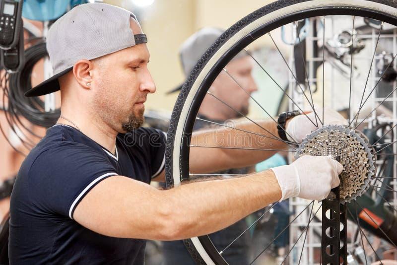 As bicicletas do técnico de reparo eram loja reparada da bicicleta da engrenagem imagens de stock royalty free