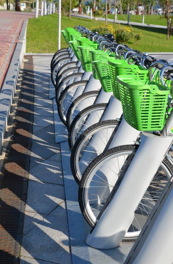 As bicicletas são estacionadas com cestas verdes fotografia de stock