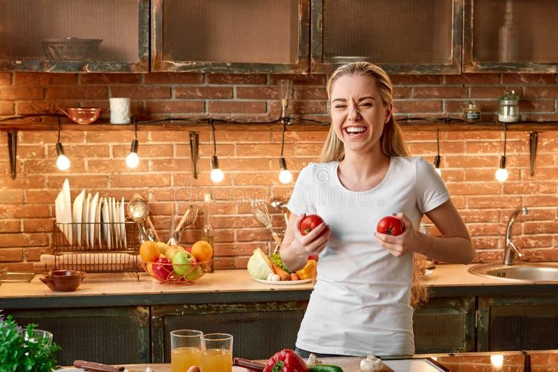 As boas escolhas do alimento são bons investimentos Jovem mulher feliz que cozinha vegetais na cozinha moderna Interior acolhedor foto de stock royalty free