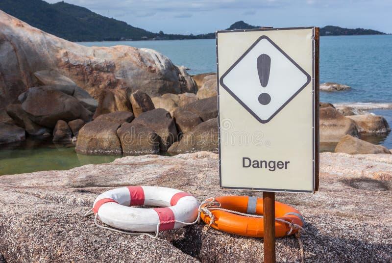 As boias de vida alaranjadas e brancas na rocha com sinal do perigo advertem foto de stock royalty free
