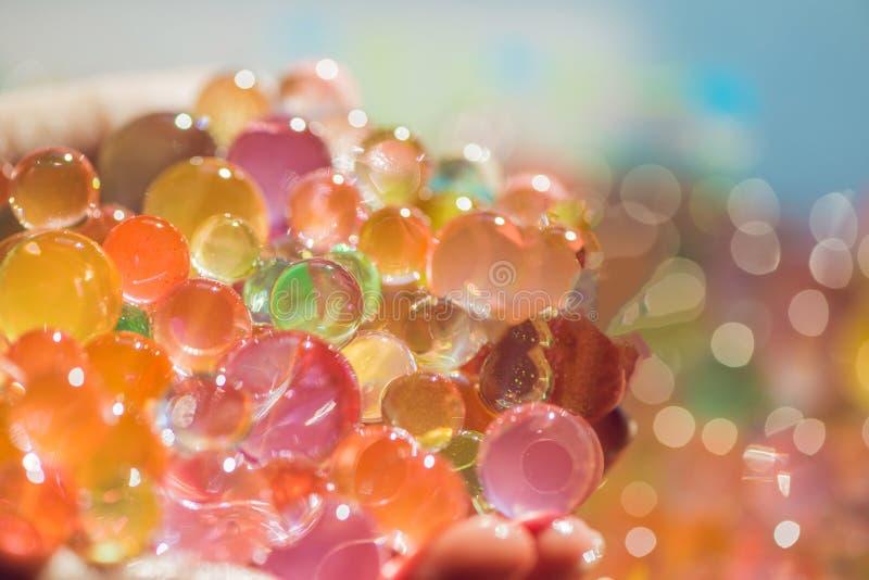 As bolas coloridas da água perlam, hydrogel dentro nas mãos Expe sensorial imagens de stock royalty free