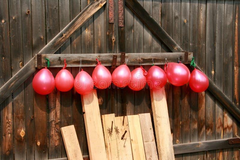 As bolas estão pendurando em uma porta de madeira Dardos do lance no alvo imagens de stock royalty free