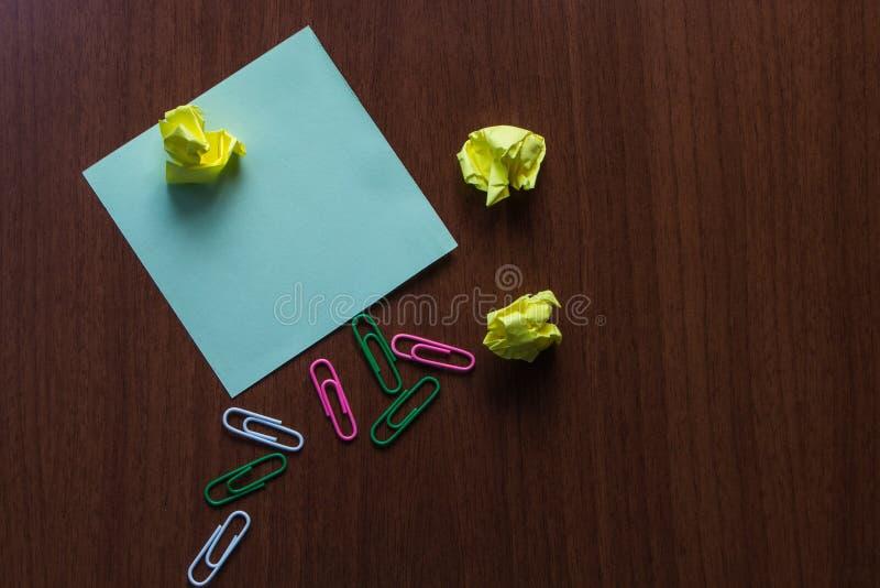 As bolas pequenas do papel da vista três superiores coloriram grampos colam a almofada que encontra-se na tabela de madeira Excel imagem de stock royalty free