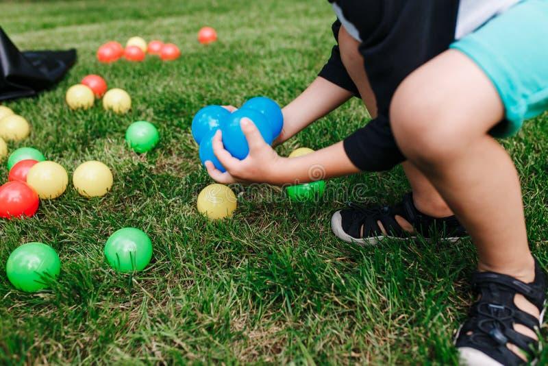 As bolas plásticas coloridas do brinquedo derramaram na grama Menino que gethering bolas azuis Atividade da festa de anos do bebê fotos de stock royalty free