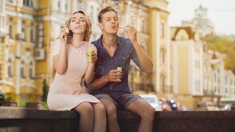 As bolhas de sopro dos pares alegres despreocupados, apreciando a liberdade e a juventude, amam imagens de stock royalty free