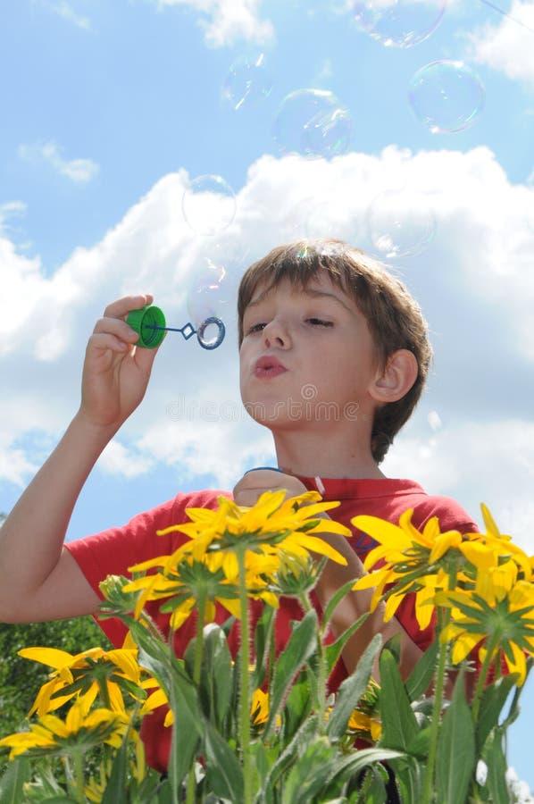 As bolhas do menino e de sabão fotografia de stock