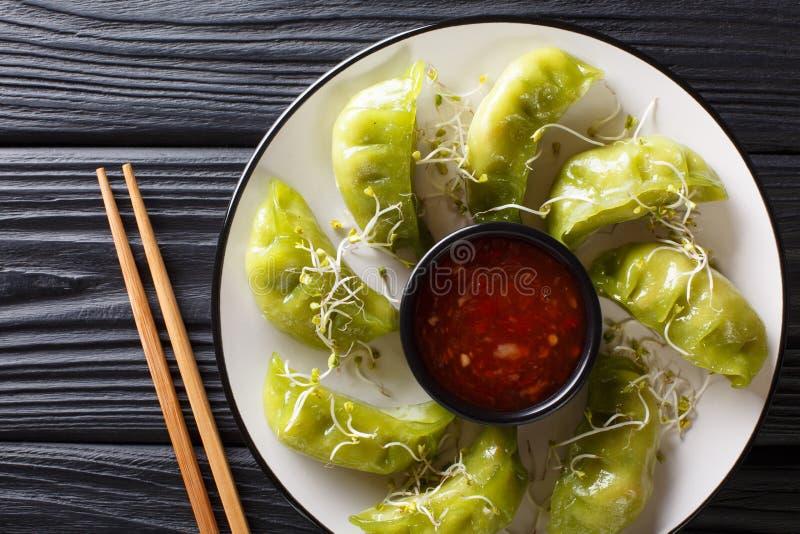 As bolinhas de massa verdes frescas do gyoza com matcha são servidas com molho de pimentão picante e microgreen o close-up na tab foto de stock