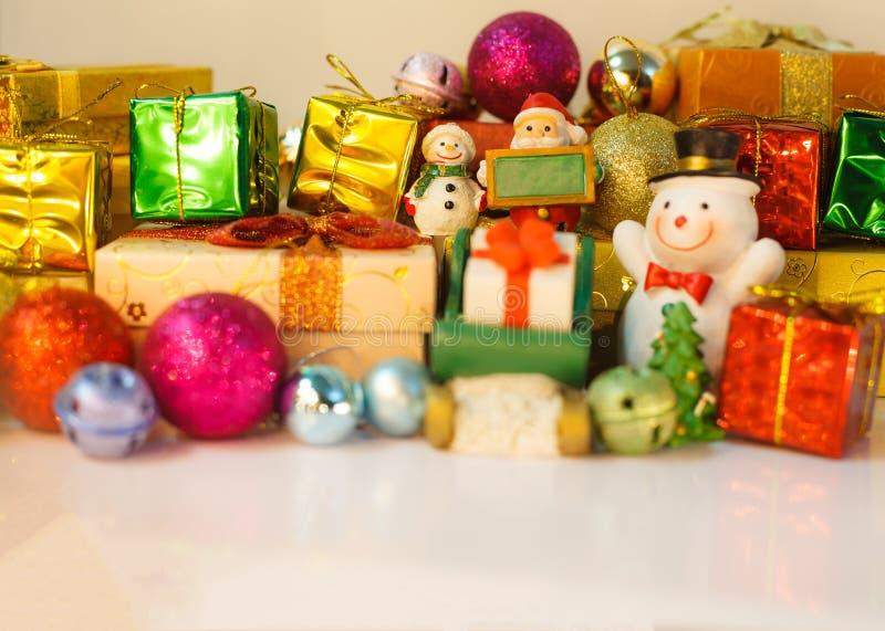 As bonecas de Santa Claus e do boneco de neve entregam bons presentes das crianças na Noite de Natal, fundo com as caixas decorad fotos de stock