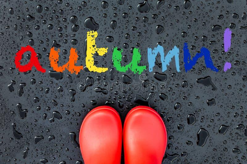 As bordas das botas de borracha vermelhas estão em uma superfície molhada molhada coberta com os pingos de chuva fotos de stock