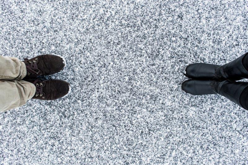 As botas masculinas e fêmeas que estão no asfalto cobriram a superfície corajoso da neve Nevado áspero Textplace Inverno frio Vis foto de stock royalty free