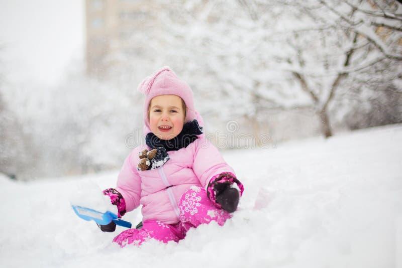 As brincadeiras com neve no inverno Uma menina em um revestimento brilhante e em um chapéu feito malha, trava flocos de neve em u fotografia de stock royalty free