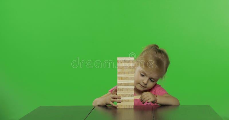 As brincadeiras o jenga A menina puxa blocos de madeira de uma torre imagens de stock royalty free
