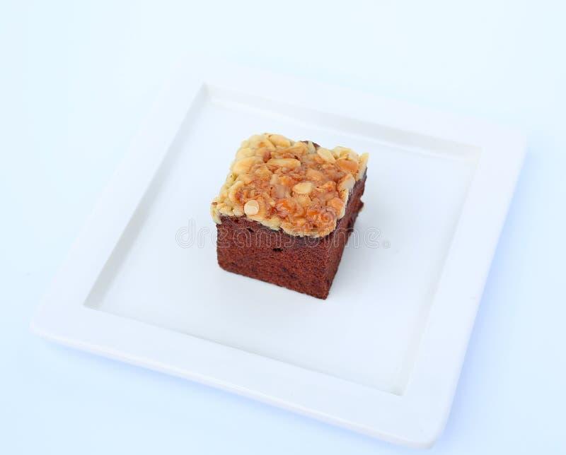 As brownies do chocolate na placa do quadrado branco, bolo da brownie cobriram com porcas fotos de stock royalty free