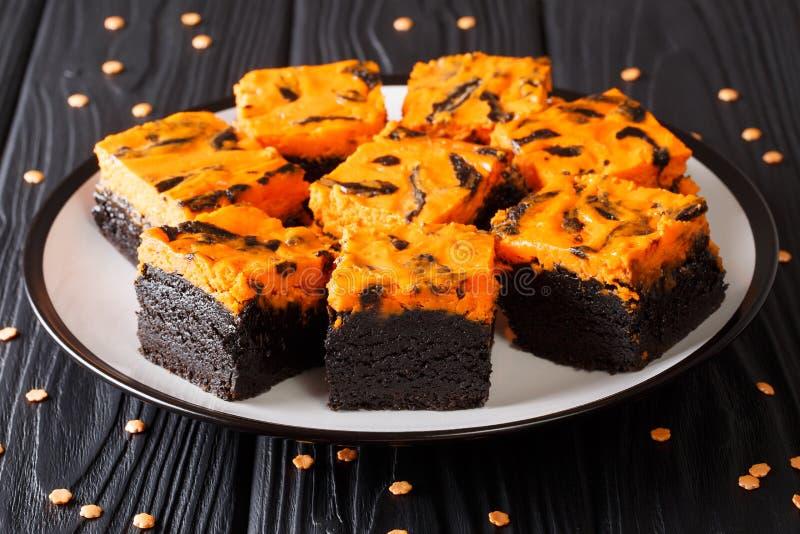 As brownies do queijo creme da doçura de Dia das Bruxas endurecem o preto com laranja imagens de stock