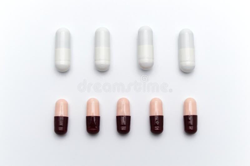 As cápsulas de diferentes cores entre cápsulas brancas e o castanho avermelhado escuro e o rosa macio misturam-se entre si imagens de stock