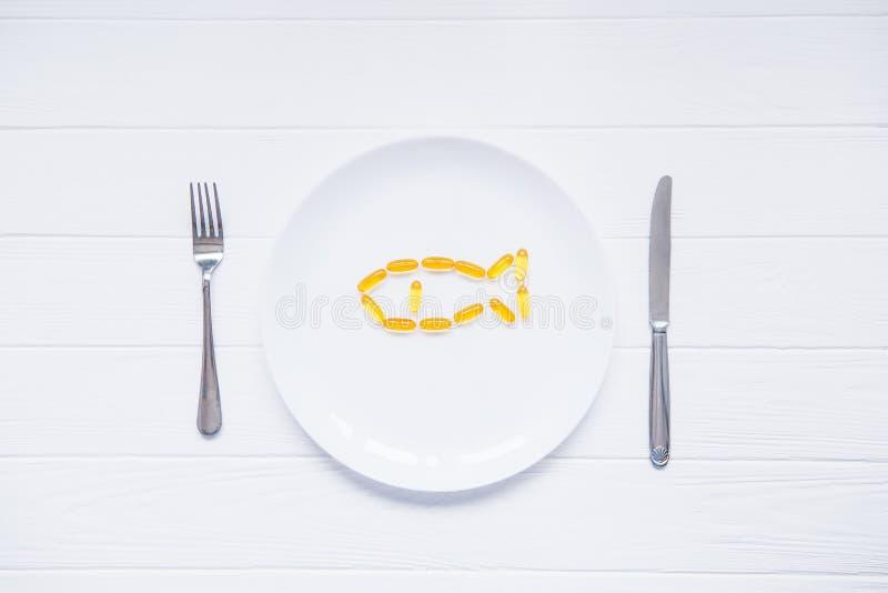 As cápsulas do óleo de fígado de bacalhau da vista superior, ômega 3, vitamina D na forma dos peixes na placa redonda branca serv imagens de stock royalty free