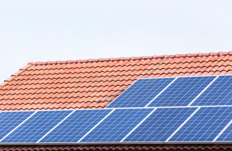 As células solares ou o photovoltaics que instalam na volta vermelha da casa de telhado de telhas concretas acima absorvem em dir imagens de stock