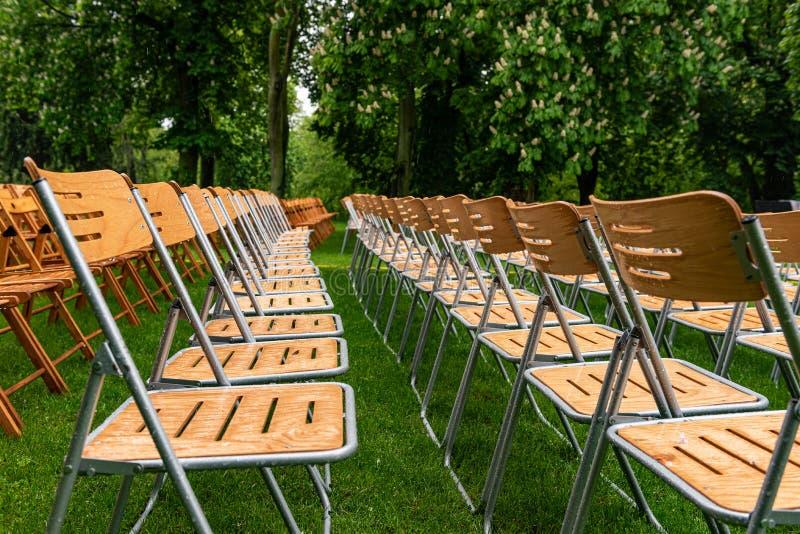 As cadeiras de madeira estão exteriores no parque na chuva Auditório vazio, grama verde, árvores e gotas da água fotos de stock