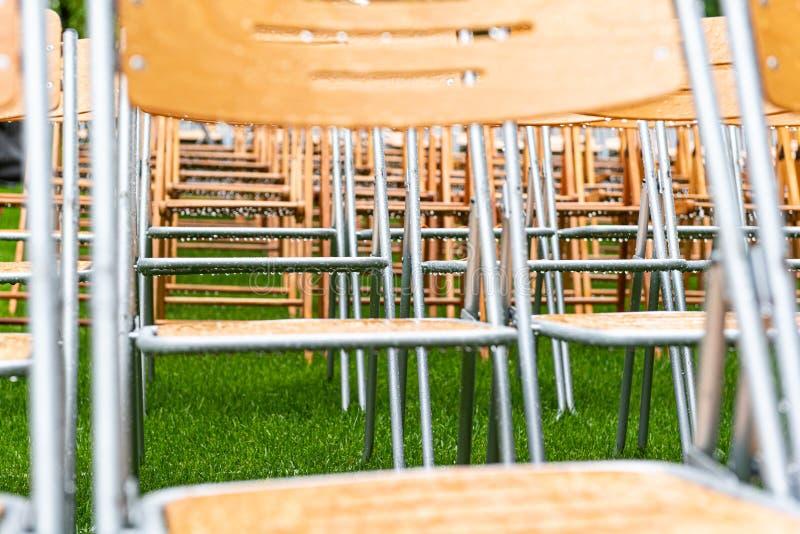 As cadeiras de madeira estão exteriores no parque na chuva Auditório vazio, grama verde, waterdrops, close up imagem de stock