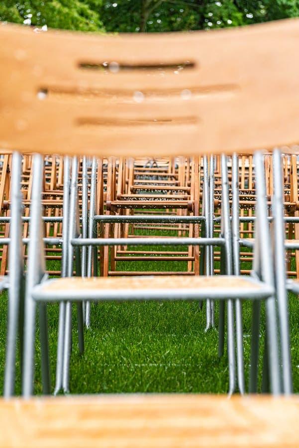 As cadeiras de madeira estão exteriores no parque na chuva Auditório vazio, grama verde, waterdrops, close up fotos de stock