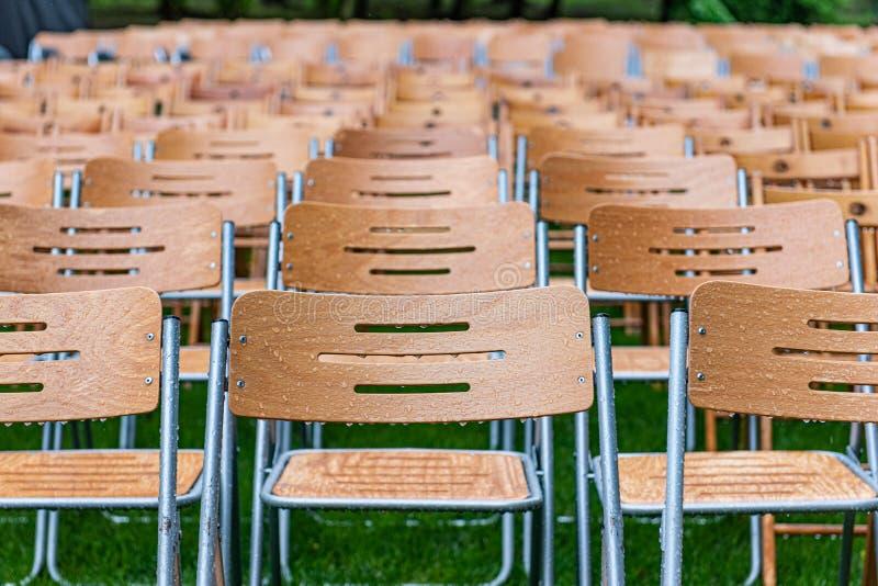 As cadeiras de madeira estão exteriores no parque na chuva Auditório vazio, grama verde, waterdrops, close up foto de stock royalty free