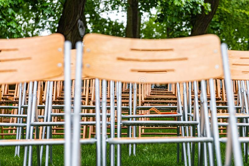 As cadeiras de madeira estão exteriores no parque na chuva Auditório vazio, grama verde, waterdrops, close up imagens de stock