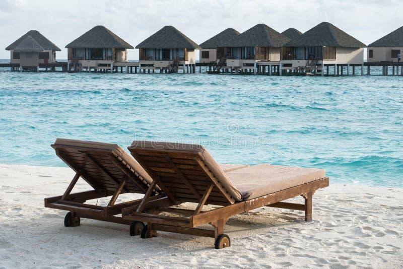 As cadeiras de madeira na areia branca encalham com fundo das casas de campo da água fotos de stock