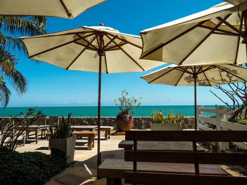 As cadeiras de praia bonitas com o guarda-chuva na areia branca tropical encalham foto de stock