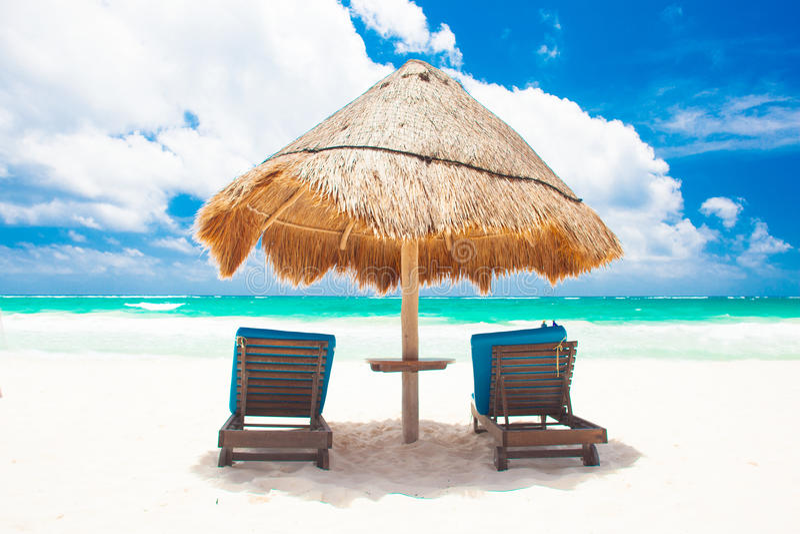 As cadeiras e o guarda-chuva na areia branca encalham em Tulum imagens de stock