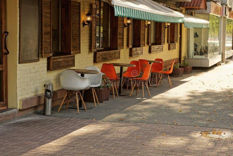 As cadeiras e as tabelas coloridas estão na rua no passeio contra a parede com janelas fotografia de stock royalty free