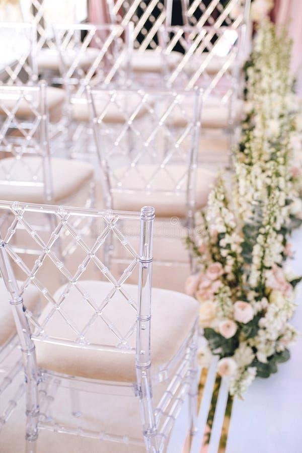 As cadeiras transparentes do desenhista com rombo modelam o vvide na área de arranjos de flor da decoração do casamento fotografia de stock