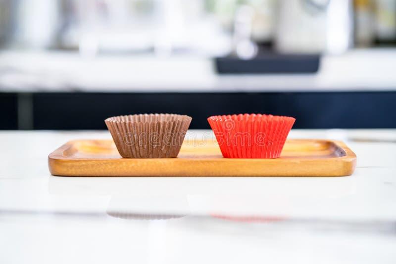 As caixas de papel coloridas para cozem queques na bandeja de madeira foto de stock royalty free