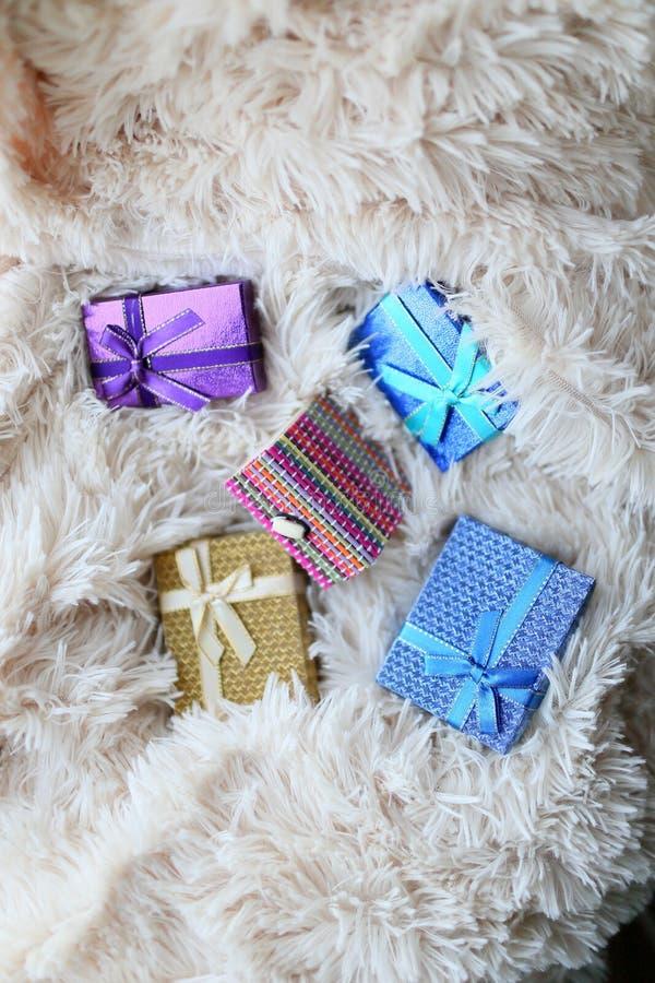 As caixas de presente coloridas dispersaram na pele brilhante macia da manta imagem de stock royalty free