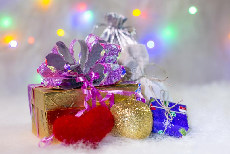As caixas de presente com uma grande curva vermelha contra um bokeh do fundo do twinkling party luzes imagem de stock royalty free