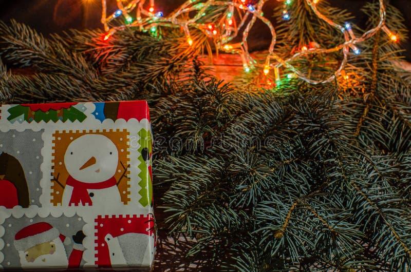 As caixas de presente com uma grande curva vermelha contra um bokeh do fundo do twinkling party luzes Presente luxuoso do ano nov fotos de stock royalty free