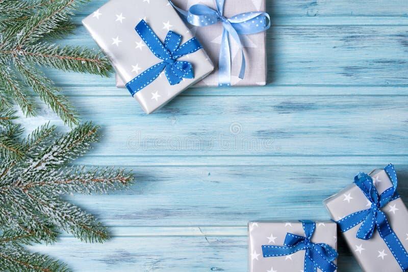 As caixas de presente e o abeto do Natal ramificam com neve, fundo de madeira, vista superior imagem de stock royalty free