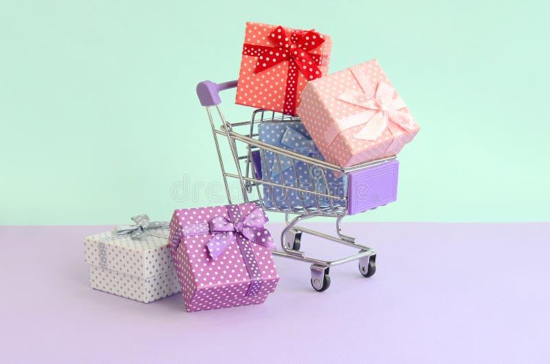 As caixas de presente pequenas de cores diferentes com fitas encontram-se no carrinho de compras em um fundo pastel violeta e azu imagem de stock
