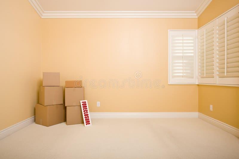 As caixas moventes e a execução duma hipoteca assinam dentro o quarto vazio foto de stock