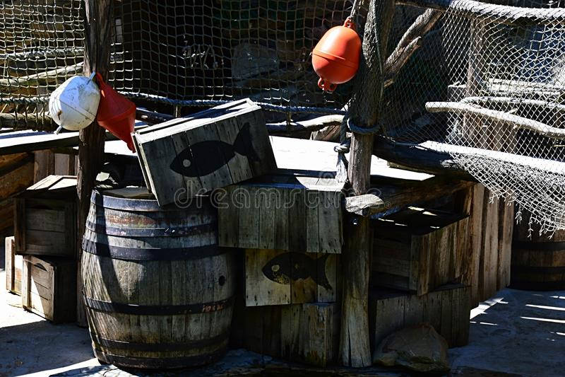 As caixas, os tambores, as boias e as redes de pesca da pesca arranjaram na exposição fotografia de stock royalty free